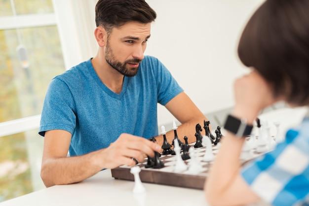 ひげを生やした父と息子がテーブルの上でチェスをしています。 Premium写真