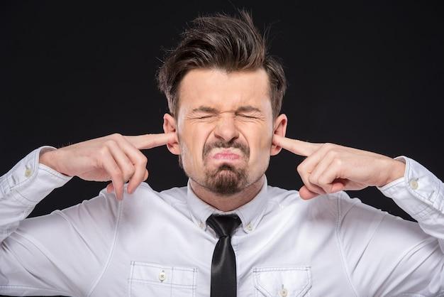 若い男は、うるさいので耳を閉じます。 Premium写真