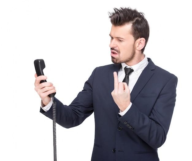 感情的な若い男が電話で叫んでいます。 Premium写真