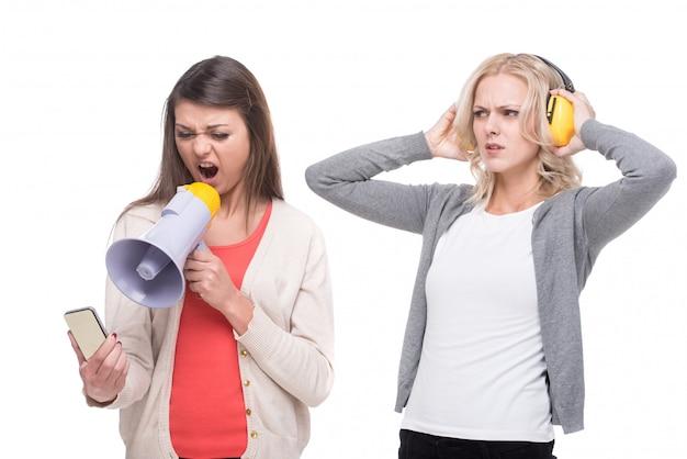 Сердитая женщина кричит по телефону через мегафон. Premium Фотографии