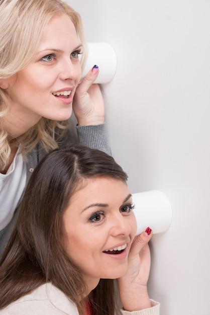Две молодые женщины используют стакан как телефон. Premium Фотографии