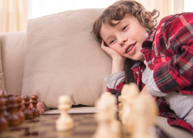 賢い少年はチェスをしながら笑っています。 Premium写真
