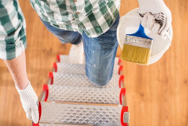 男の平面図は、ペイントブラシで梯子の上に立っています。 Premium写真