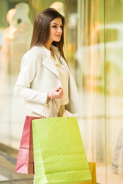 ショッピングモールで買い物袋を持つ美容女性。 Premium写真