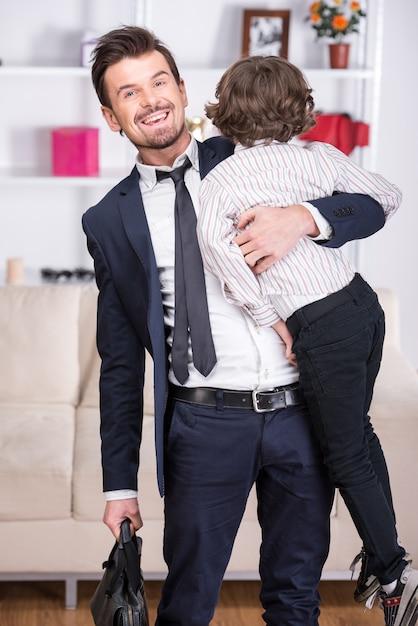 幼い息子は仕事から彼のビジネスマンの父に会います。 Premium写真