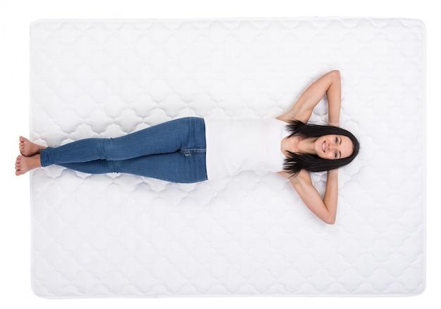 若い女性は白いベッドに横たわっています。 Premium写真