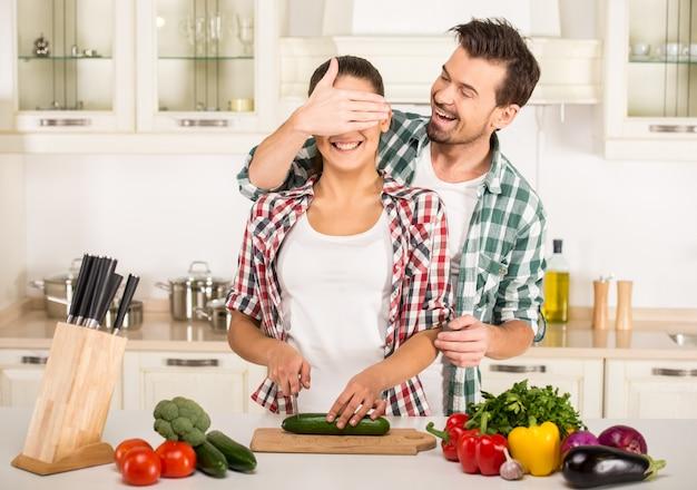 Молодая женщина и муж готовят со свежими овощами. Premium Фотографии