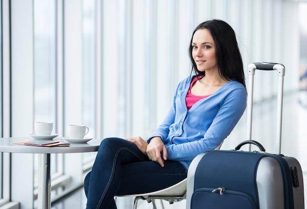 Молодая женщина сидит в аэропорту с кофе. Premium Фотографии