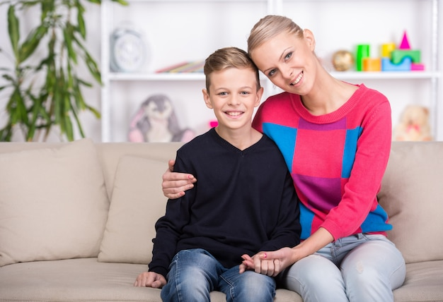 美しい母親と彼女の息子は自宅のソファーに座っています。 Premium写真