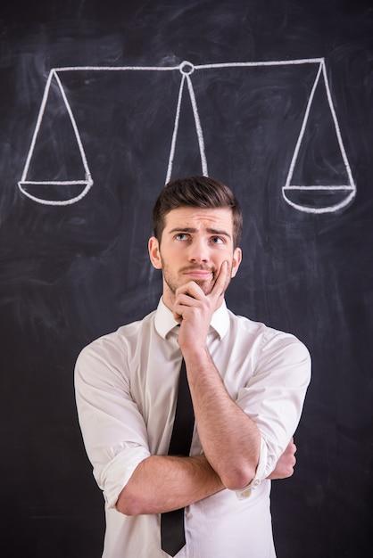 男は重量を図面で黒板に立っています。 Premium写真