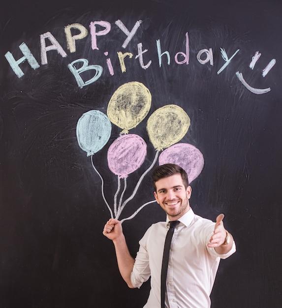 男は風船とお誕生日おめでとうを描画に対して立っています。 Premium写真