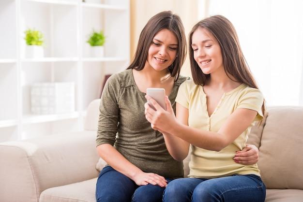 母と彼女のかわいい十代の娘は電話を見ています。 Premium写真
