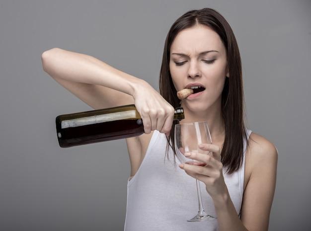 Молодая женщина наливает вино в бокал. Premium Фотографии