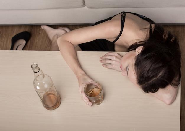 うつ病の若い美しい女性は、アルコールを飲んでいます。 Premium写真