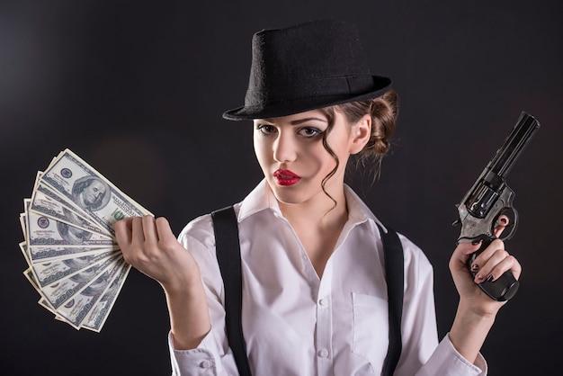 若い女性ギャング銃を保持し、お金を数えます。 Premium写真