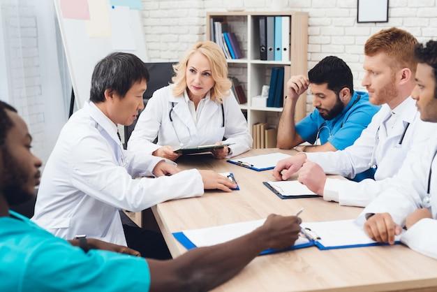 さまざまな人種の医師のグループがテーブルで会っています。 Premium写真