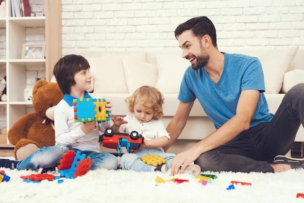Папа и двое его сыновей играют в игрушки дома. Premium Фотографии