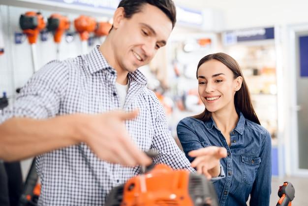 店の売り手は、顧客に芝刈り機を見せます。 Premium写真