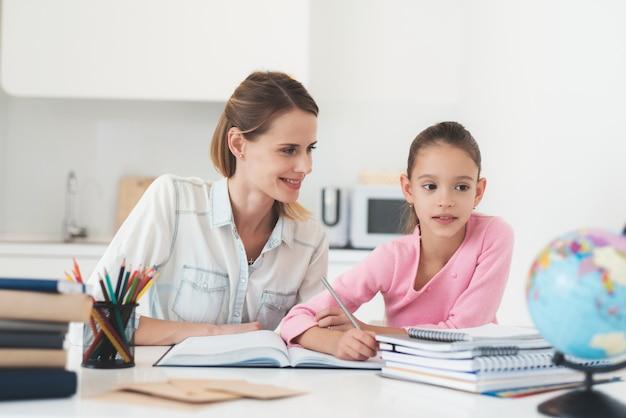 お母さんは娘が台所で宿題をするのを助けます。 Premium写真