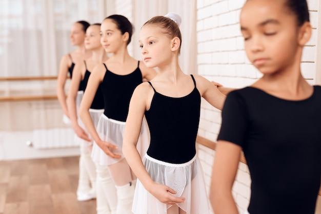 バレエのクラスでリハーサルする若いバレリーナ。 Premium写真