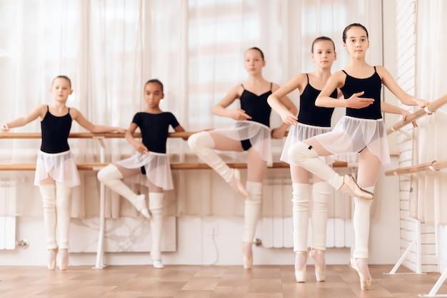 バレエクラスの若いバレリーナは、一緒にトレーニングします。 Premium写真