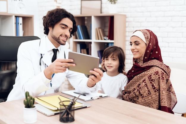 アラブの医者はタブレットに何かを示しています。 Premium写真