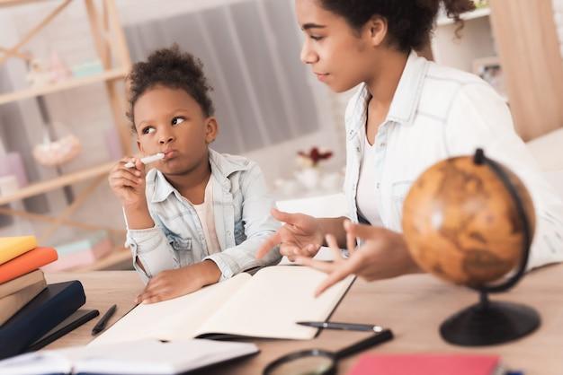 ママと娘は一緒に学校で宿題をします。 Premium写真