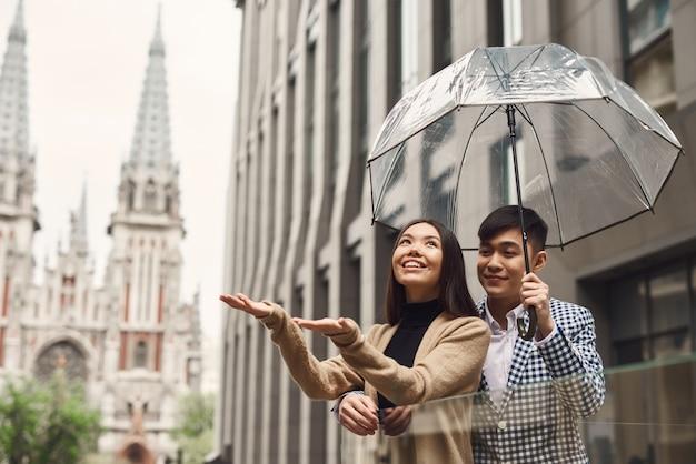 旧市街の男の子と女の子の雨の日のロマンチックな旅行。 Premium写真