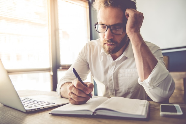 眼鏡で疲れたビジネスマンは彼のノートに書いています Premium写真