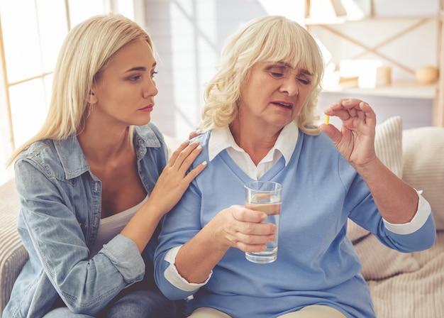 女の子は薬を飲んでいる悲しい古い母親を落ち着かせています Premium写真