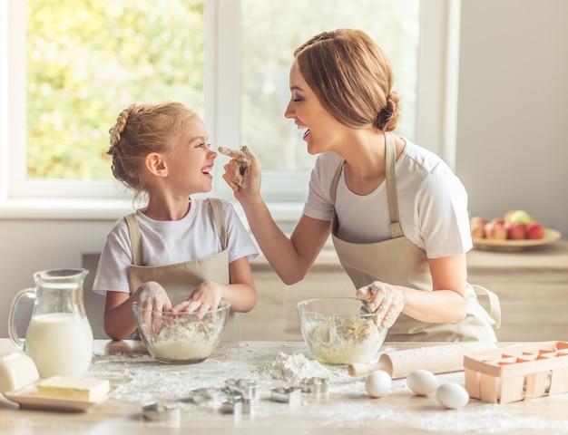 エプロンでかわいい女の子と彼女の美しいお母さんが遊んでいます。 Premium写真