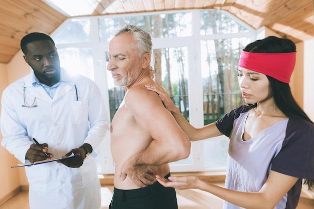 医者は彼の背中に腰痛を持っている老人を診察します。 Premium写真