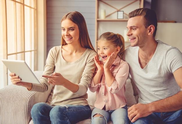 Родители и их маленькая дочь с помощью цифрового планшета Premium Фотографии
