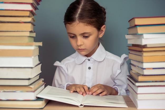 学校の制服を着た魅力的な少女は本を読んでいます。 Premium写真
