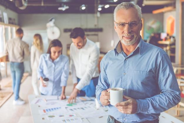 ハンサムな成熟した実業家は一杯のコーヒーを保持しています。 Premium写真