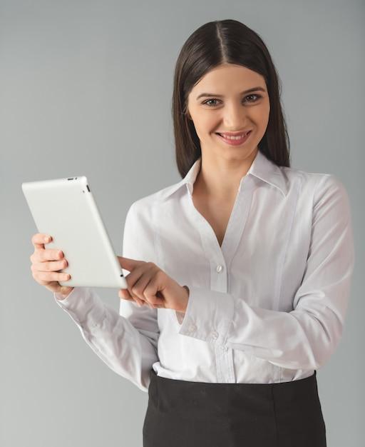 Женщина в формальной одежде использует цифровой планшет Premium Фотографии