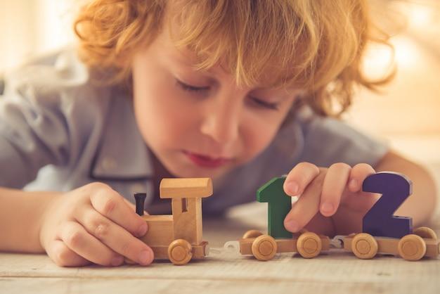 Мальчик играет с игрушечным деревянным поездом и номерами дома Premium Фотографии