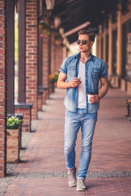 ジーンズの服でスタイリッシュな男の完全な長さの肖像画 Premium写真