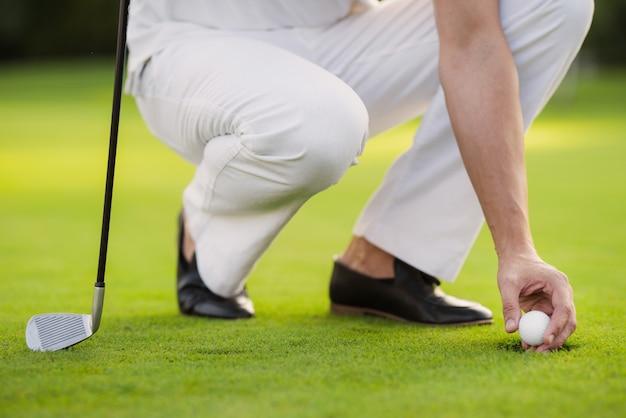 閉じる。男が穴からボールを取り出す Premium写真
