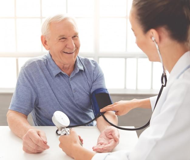 医者は診療所で年配の患者の脈をチェックします Premium写真
