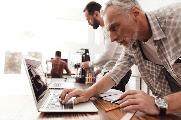 Человек руководит процессом запуска и печати принтера. Premium Фотографии