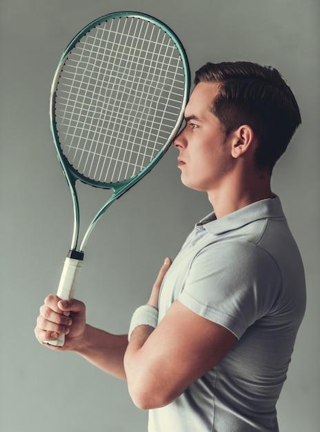 Человек играет в теннис Premium Фотографии
