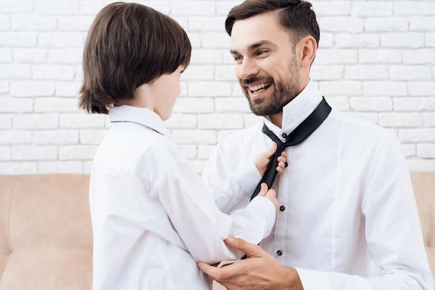 Красивый папа и сын в одной одежде. Premium Фотографии