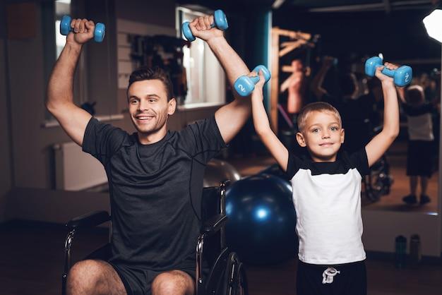 父と息子はダンベル運動をしています。 Premium写真