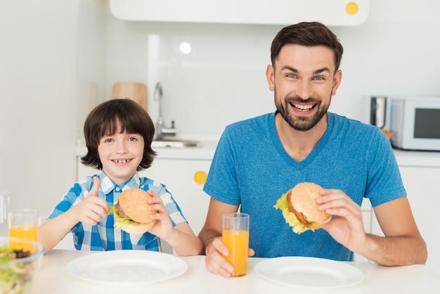 少年とパパは明るいキッチンでハンバーガーを食べる Premium写真