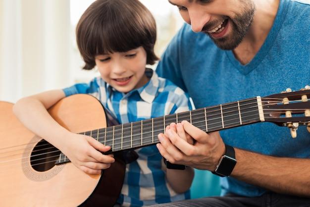 父は息子にギターを弾くように教えます Premium写真