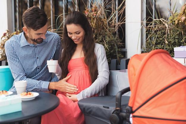 男性と妊娠中の女性はカフェのテーブルに座っています。 Premium写真