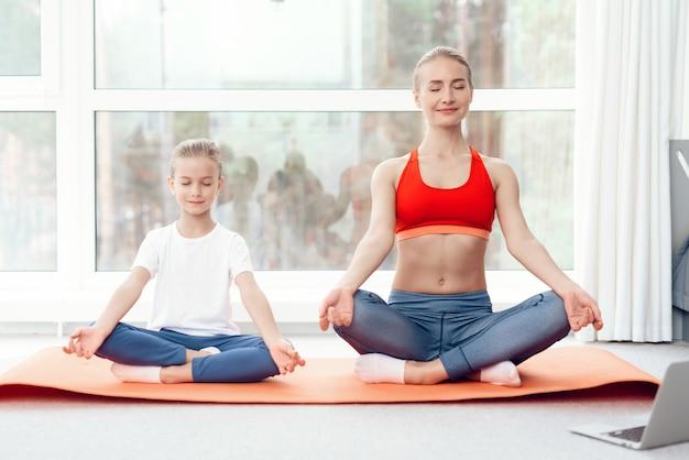Мама и дочка занимаются йогой в спортивной одежде Premium Фотографии