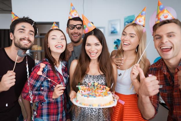 誕生日の女の子はろうそくでケーキを持っています。 Premium写真