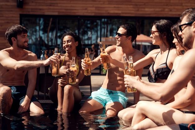 プールサイドでアルコール飲料を持つ若い友達 Premium写真